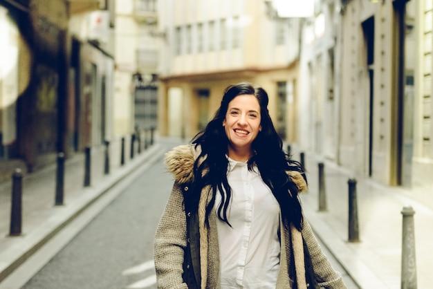 Femme d'âge moyen souriant et riant joyeusement en marchant dans la ville.