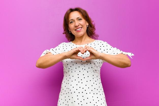 Femme d'âge moyen souriant et se sentant heureux, mignon, romantique et amoureux, en forme de cœur avec les deux mains contre le mur violet