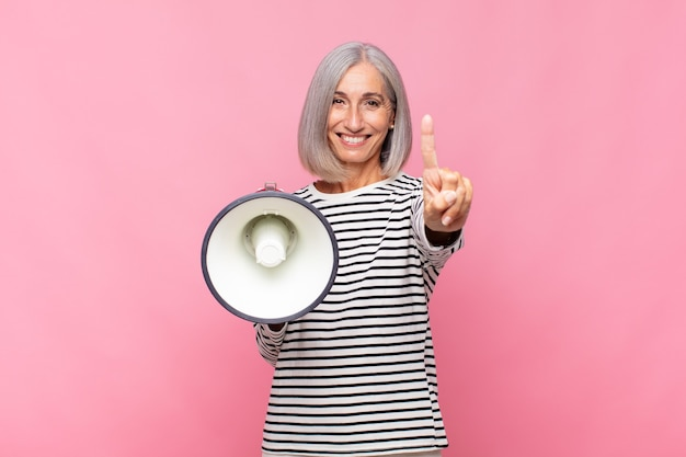 Femme d'âge moyen souriant et à la sympathique, montrant le numéro un ou d'abord avec la main vers l'avant, compte à rebours avec un mégaphone