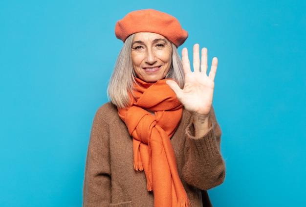 Femme d'âge moyen souriant et à la sympathique, montrant le numéro cinq ou cinquième avec la main en avant, compte à rebours