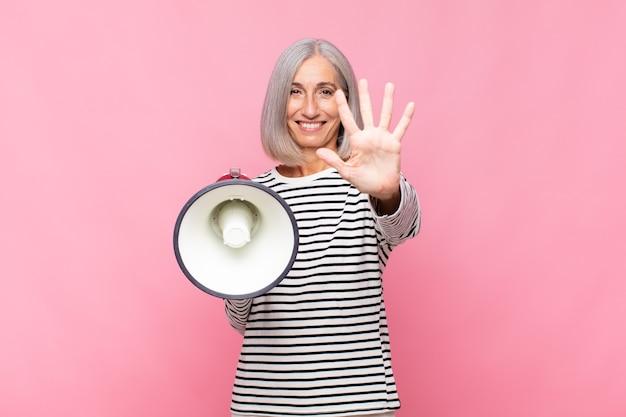 Femme d'âge moyen souriant et à la sympathique, montrant le numéro cinq ou cinquième avec la main vers l'avant, compte à rebours avec un mégaphone
