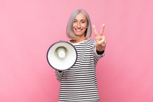 Femme d'âge moyen souriant et à la sympathique, montrant le numéro deux ou seconde avec la main vers l'avant, compte à rebours avec un mégaphone
