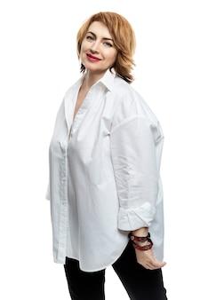 Femme d'âge moyen souriante aux cheveux rouges dans une chemise blanche