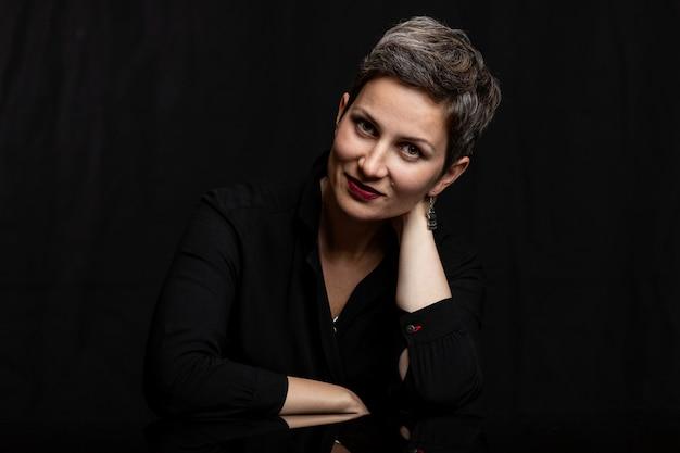Femme d'âge moyen souriante avec une coupe courte, gros plan. portrait sur fond noir.