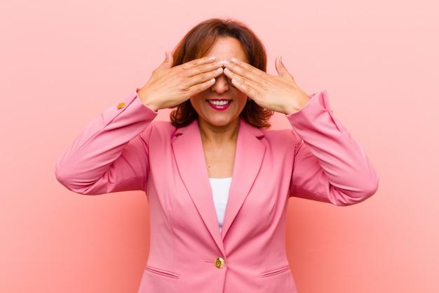 Femme d'âge moyen souriante et heureuse se couvrant les yeux avec les deux mains et attendant une surprise incroyable