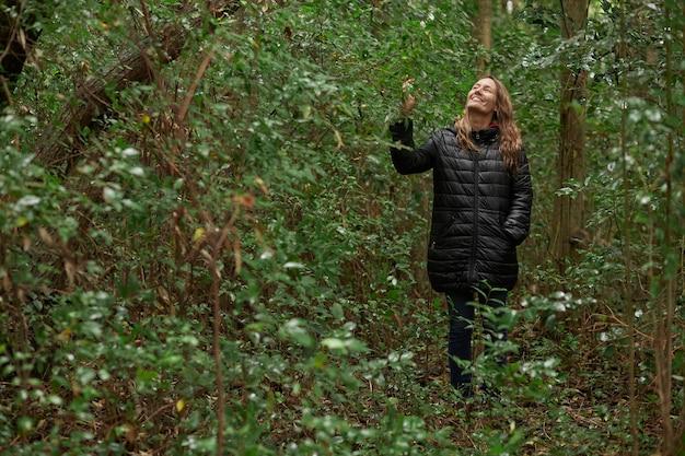 Femme d'âge moyen souriante se promenant dans les bois en hiver, tout en caressant et en profitant de la verdure. cheveux blonds caucasiens.