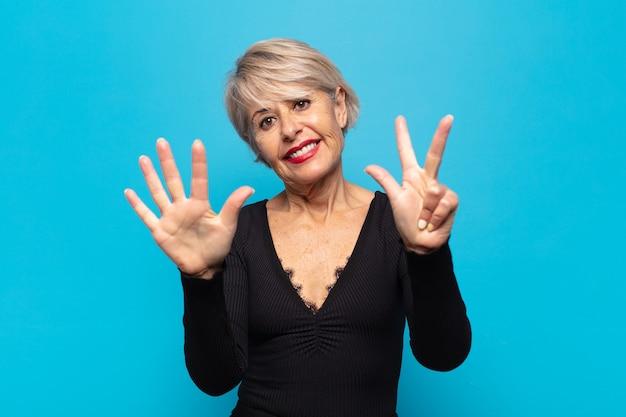 Femme d'âge moyen souriante et semblant amicale, montrant le numéro huit ou huitième avec la main vers l'avant, compte à rebours