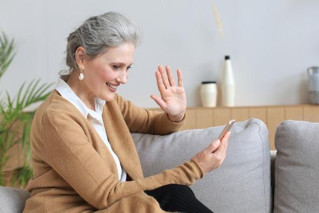 Femme d'âge moyen souriante tenant un téléphone, utilisant des applications pour appareils mobiles, regardant l'écran, assise sur un canapé.
