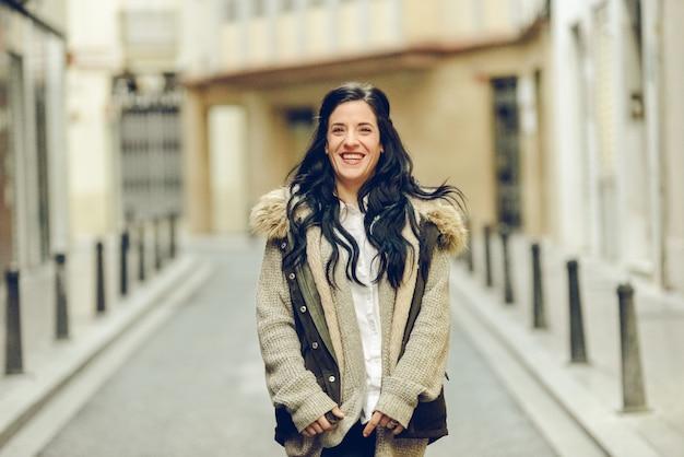 Une femme d'âge moyen sourit et rit joyeusement en se promenant dans la ville.