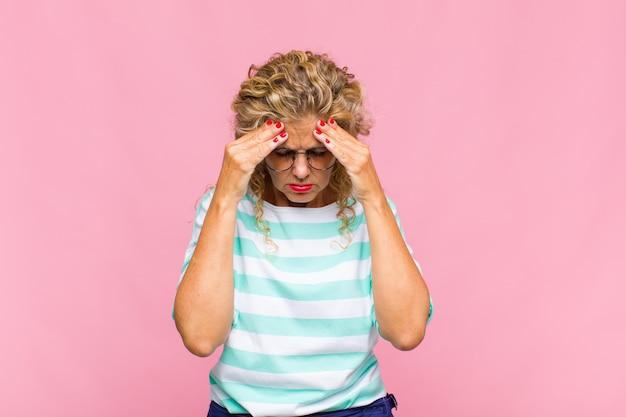 Femme d'âge moyen à la stress et frustré, travaillant sous pression avec un mal de tête et troublé par des problèmes
