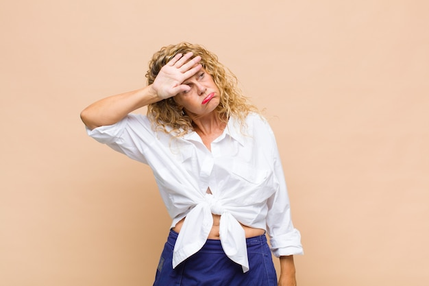 Femme d'âge moyen à stressé, fatigué et frustré, séchant la sueur du front, se sentant désespérée et épuisée