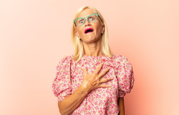 Femme d'âge moyen à la surprise et choqué, avec la mâchoire tombée tenant un objet avec une main ouverte sur le côté