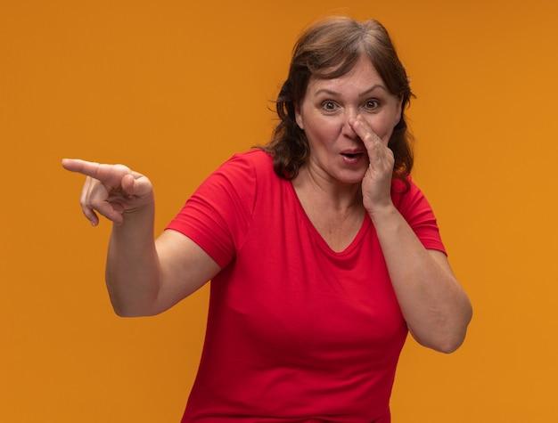 Femme d'âge moyen en t-shirt rouge souriant disant un secret avec la main près de la bouche pointant avec l'index à quelque chose debout sur le mur orange