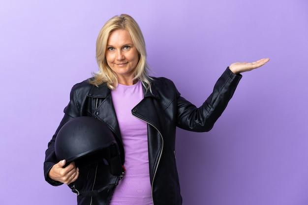 Femme d'âge moyen tenant un casque de moto isolé sur mur violet étendant les mains sur le côté pour inviter à venir