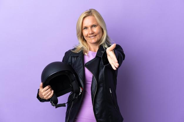 Femme d'âge moyen tenant un casque de moto isolé sur violet serrant la main pour conclure une bonne affaire