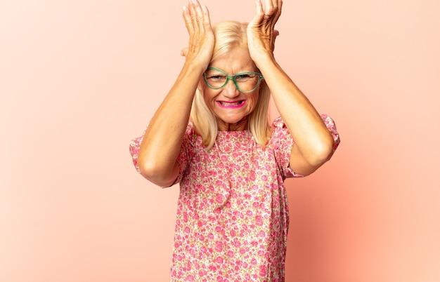 Femme d'âge moyen tenant un objet à deux mains isolé