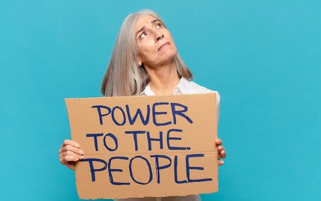 Femme d'âge moyen tenant une pancarte avec texte: pouvoir au peuple