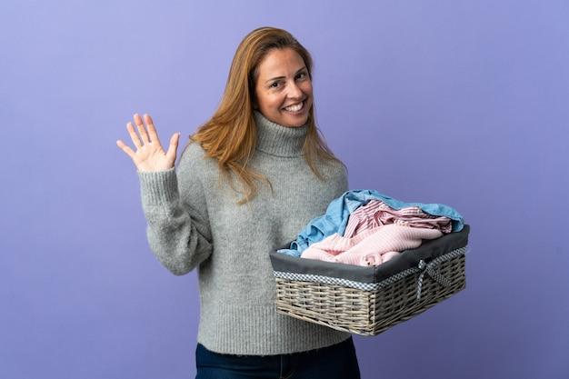 Femme d'âge moyen tenant un panier de vêtements isolé sur mur violet saluant avec la main avec une expression heureuse