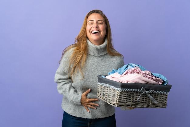 Femme d'âge moyen tenant un panier de vêtements isolé sur mur violet souriant beaucoup