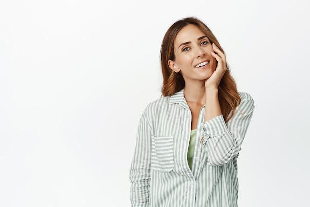 Femme d'âge moyen touchant son visage avec un sourire heureux, profitant de la douceur d'une peau du visage propre après les cosmétiques de soins de la peau