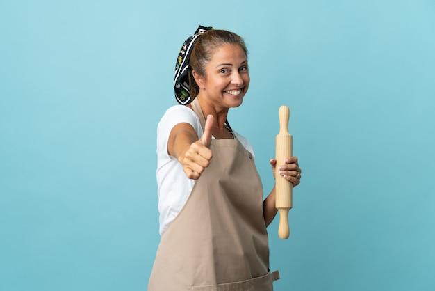 Femme d'âge moyen en uniforme de chef avec les pouces vers le haut parce que quelque chose de bien s'est passé