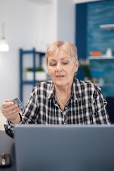 Femme d'âge moyen vérifiant un compte bancaire tenant une carte de crédit