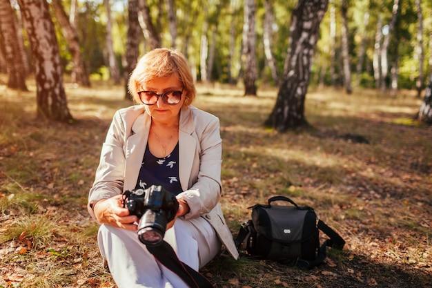 Femme d'âge moyen vérifiant les images sur la caméra dans la forêt d'automne