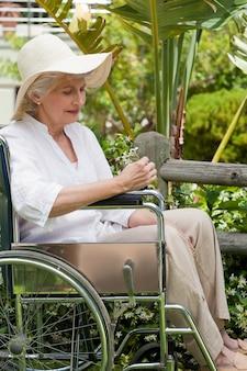 Femme d'âge mûr dans son fauteuil roulant dans le jardin