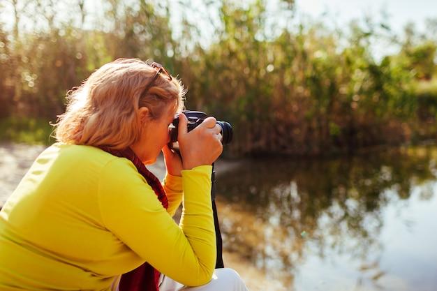 Femme d'âge mûr prenant des images sur caméra assis par rive de la rivière automne.
