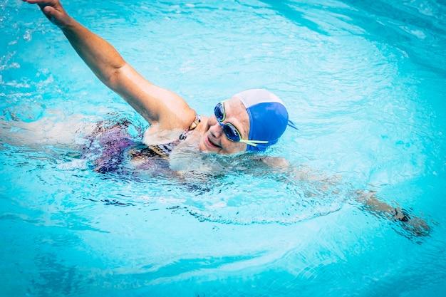 Femme âgée en activité saine nageant dans la piscine turquoise extérieure
