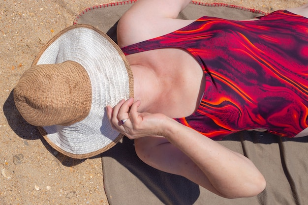 Une femme âgée adulte en maillot de bain se trouve sur le rivage sablonneux, couvrant son visage avec un chapeau. voyages et tourisme à la retraite.