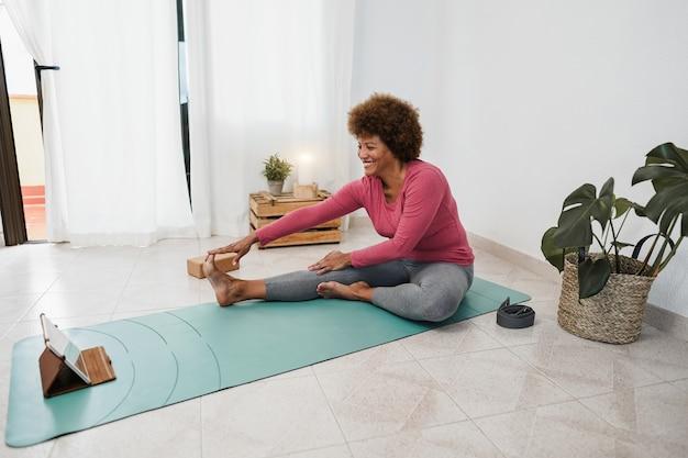 Femme âgée africaine faisant des cours de yoga en ligne à la maison - focus on face