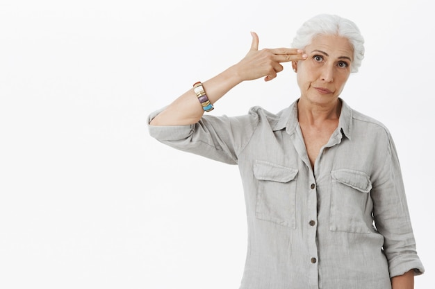 Femme âgée agacée faisant un geste de fusil de chasse sur le front