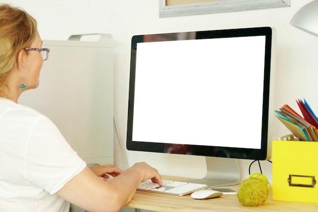 Femme âgée à l'aide d'un ordinateur à écran blanc