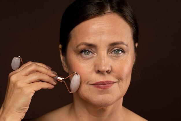 Femme âgée à l'aide d'un rouleau de quartz rose sur son visage