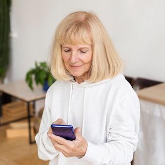 Femme âgée à l'aide de smartphone à la maison