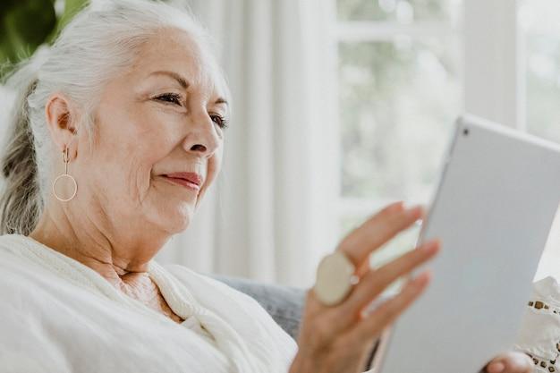 Femme âgée à l'aide d'une tablette sur un canapé