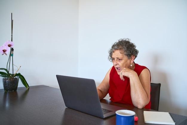 Une femme âgée a l'air surprise de l'écran d'ordinateur lors de ses achats en ligne