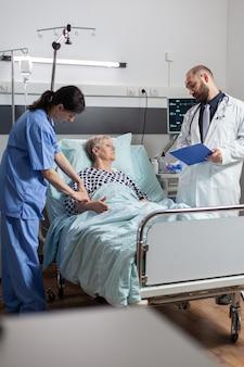 Femme âgée allongée dans un lit d'hôpital recevant des médicaments par voie intraveineuse, discutant avec un médecin du traitement et du diagnostic