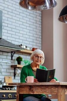 Femme âgée apaisante à lunettes et cardigan émeraude occupée à lire attentivement la bible dans la cuisine