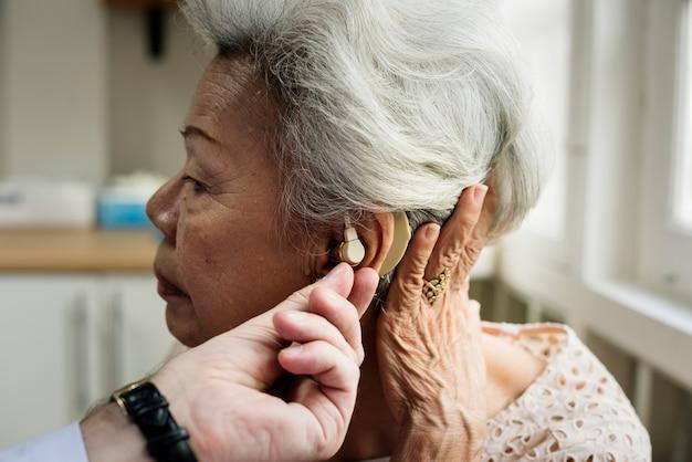 Une femme âgée avec un appareil auditif