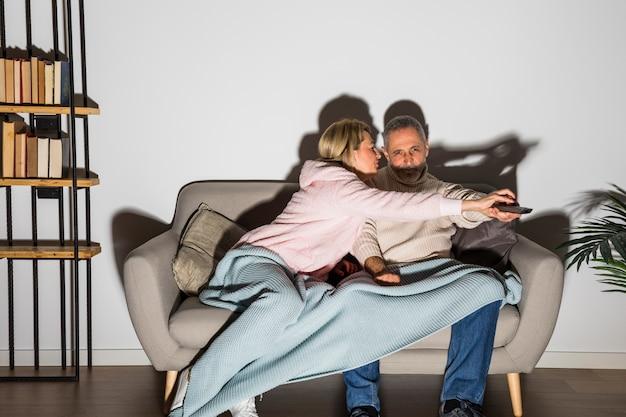 Femme âgée arrêtant un homme avec télécommande pour changer de chaîne à la télévision sur un canapé