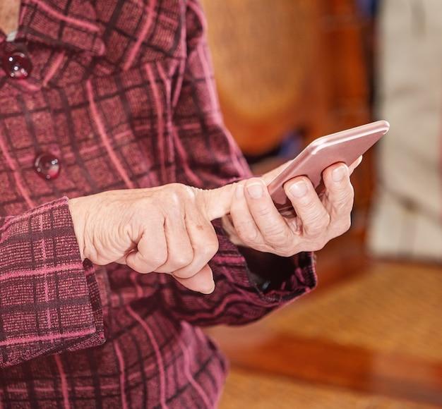 Femme âgée asiatique assise et regardant sur smartphone