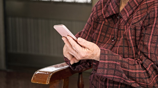 Femme âgée asiatique assise et regardant à travers quelque chose sur un smartphone moderne, établissant une connexion avec d'autres à la maison, technologie vivante, gros plan