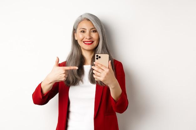 Femme âgée asiatique en blazer élégant montrant le smartphone, pointant le doigt sur le téléphone mobile et souriant, debout sur un mur blanc.