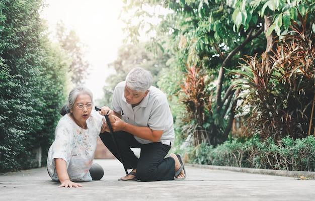Femme âgée asiatique tombant sur le sol allongé à la maison après avoir trébuché sur le pas de la porte et pleuré de douleur et son mari est venu pour aider. concept de vieille assurance et soins de santé pour personnes âgées