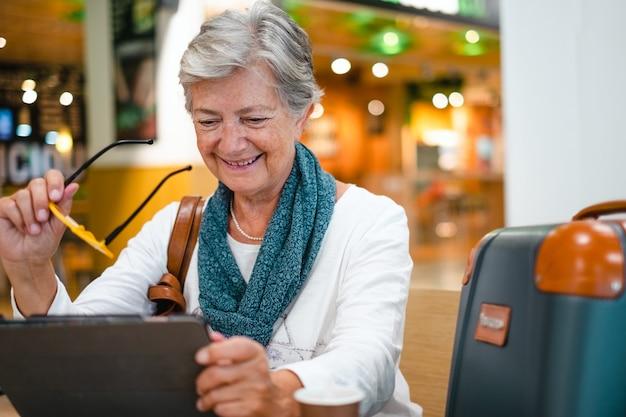 Femme âgée assise au café de l'aéroport à l'aide d'une tablette numérique en attendant l'embarquement. le voyageur mûr heureux boit du café
