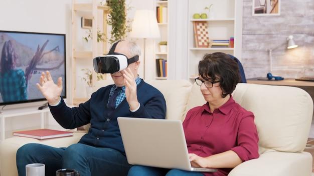 Femme âgée assise sur un canapé à l'aide d'un ordinateur portable pendant que son mari fait l'expérience de la réalité virtuelle pour la première fois