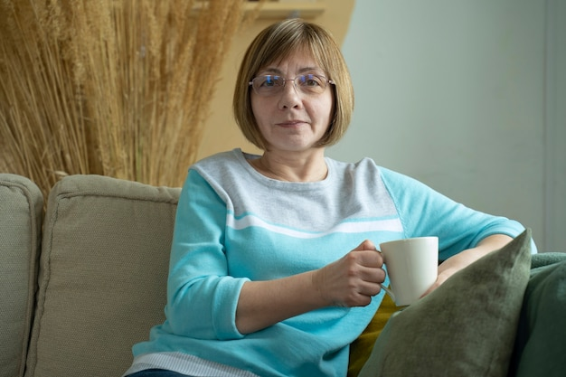 Femme âgée assise sur le canapé dans son salon et tenant une tasse de café tout en souriant à la caméra