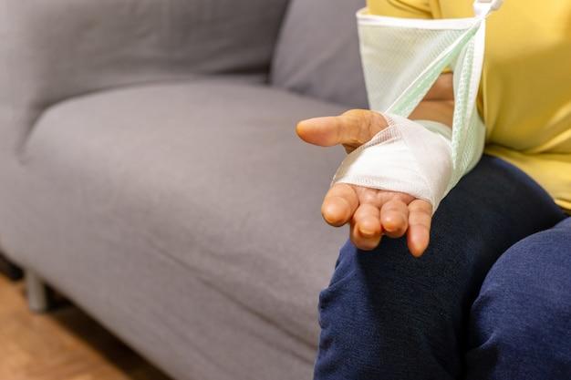 Femme âgée assise sur le canapé avec la main blessée sur un plâtre.